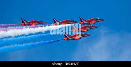 Red arrows hawks display team in arrow formation from left to  right trailing pink blue and white smoke - blue sky - Stock Photo