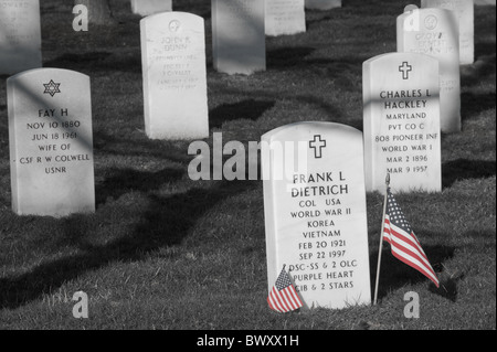 Small American flags stand next to a gravestone in Arlington National Cemetery, in Arlington, Virginia. - Stock Photo