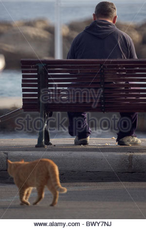 Person sitting bench greece - Stock Photo