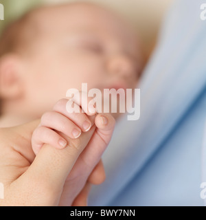 Baby holding Mother's Hand - Stock Photo