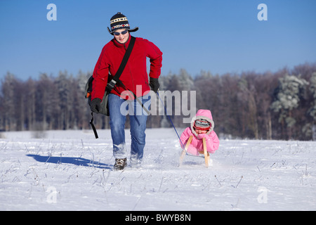 Woman pulling infant girl on wooden sled in winter landscape, Dobel, Black Forest, Gerrmany - Stock Photo
