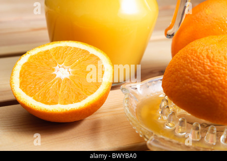 A jug of orange juice with whole and cut oranges and an orange squeezer on a wooden table. - Stock Photo