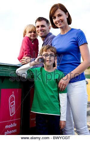 A young boy using a mobile phone in a recycling centre - Stock Photo