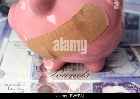 sticking plaster on pink piggy bank on british 20 pound notes - Stock Photo