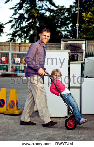 A father pushing his daughter on a trolley in a recycle center - Stock Photo
