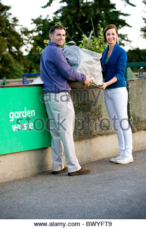 A mid-adult couple recycling garden waste - Stock Photo