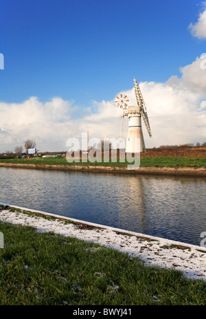Thurne Mill and reflection on the Norfolk Broads in winter set against building shower clouds. - Stock Photo