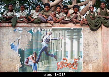 Rural Indian village school children sitting on their school wall. Andhra Pradesh, India - Stock Photo