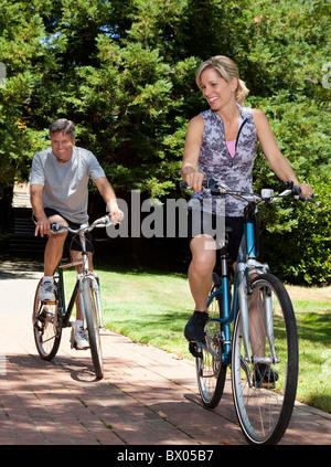 Caucasian couple riding bicycles - Stock Photo