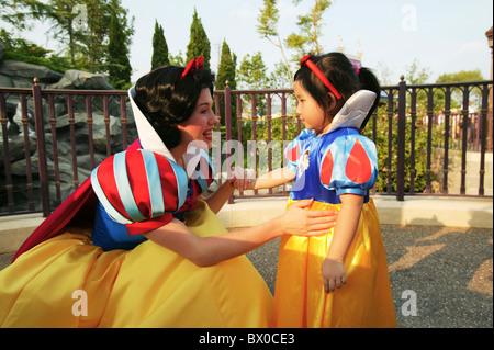 Princess Snow White greeting a girl who dress the same, Fantasyland, Hong Kong Disneyland, Lantau Island, Hong Kong, - Stock Photo