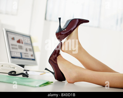 woman taking off shoes in office - Stock Photo