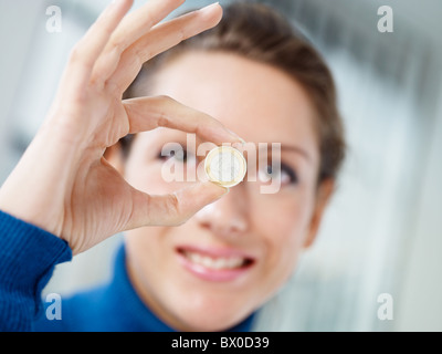 woman holding one euro coin
