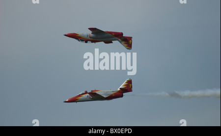 Two Spanish Aerobatic Air Force Team planes Aguilla Casa 101 Aviojet mirroring each other flying along in parallel - Stock Photo