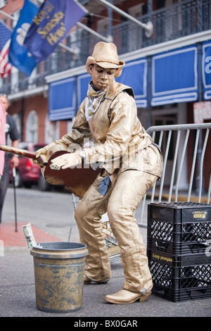 Men painted in gold/silver perform for tips on Bourbon Street in New Orleans, Louisiana's French Quarter. - Stock Photo