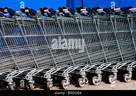 a line of empty supermarket shopping carts against blue wall - Stock Photo