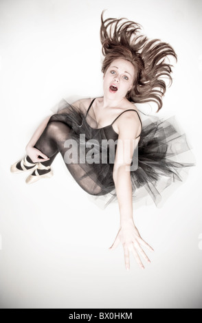 A teenage caucasian ballerina wearing a black tutu jumps in the air. - Stock Photo