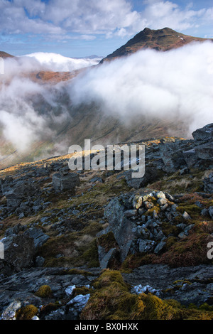 The summit of Beinn Ime, a Munro in the Arrochar Alps in the southern highlands of Scotland, appears above a sea - Stock Photo