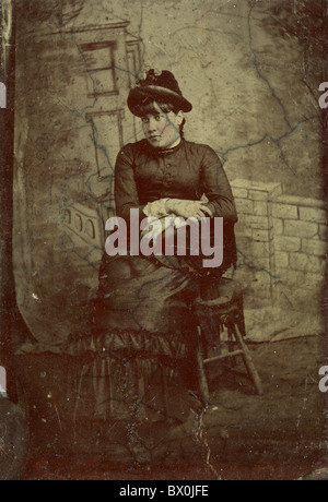 woman wearing black dress with hat 1860s 1870s 1880s vertical portrait black and white tin type photograph victorian - Stock Photo