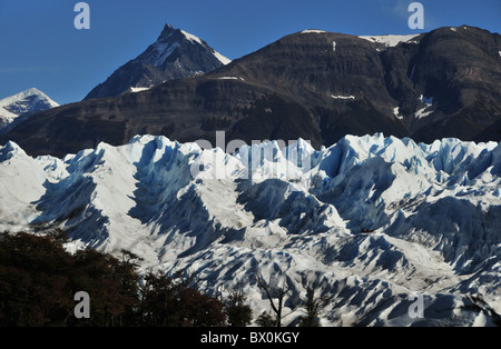 Group of distant ice-trekkers on the corrugated surface of the Perito Moreno Glacier, below a backdrop of rocky - Stock Photo