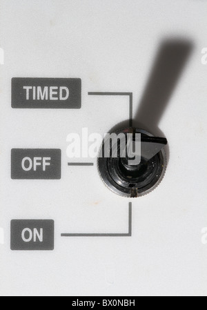 Toggle switch on heating control system with timed, on and off settings. - Stock Photo
