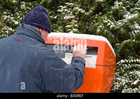 A man posting a letter during a snow shower in the Netherlands - Stock Photo