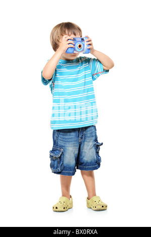 Full length portrait of a little boy taking pictures with a camera - Stock Photo