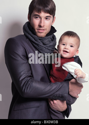Fashion portrait of a young man wearing a black blazer and a scarf with a baby boy in his hands - Stock Photo