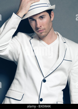 Fashion photo of a young man wearing a white blazer and a hat - Stock Photo