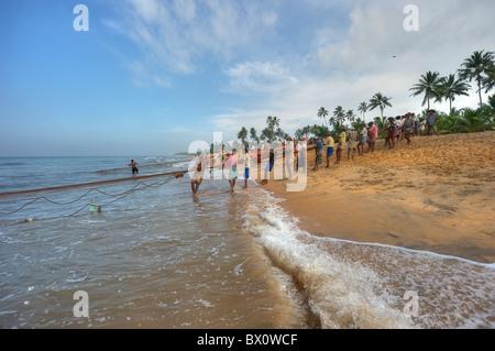 People pulling a fishing net in the southern coast of Sri Lanka - Stock Photo