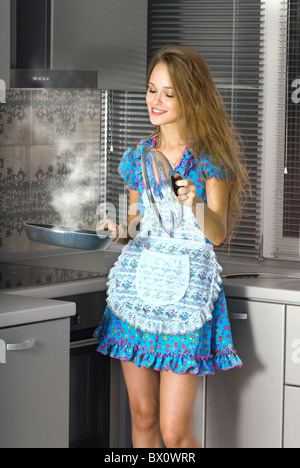 beautiful happy housewife with serving spoon in the kitchen - Stock Photo