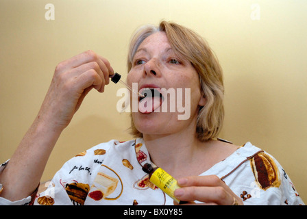 Woman taking a homeopathic remedy - Stock Photo