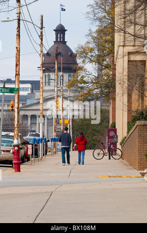Two people walk along Main Street toward the State House in Columbia, SC, in front of a USC campus science building. - Stock Photo