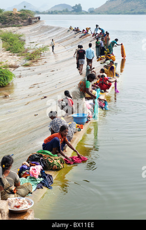 Indian women and girls washing clothes by hand in a lake. Andhra Pradesh, India - Stock Photo