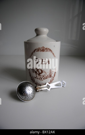 Jar of tea on white kitchen surface with stainless steel tea strainer in front - Stock Photo