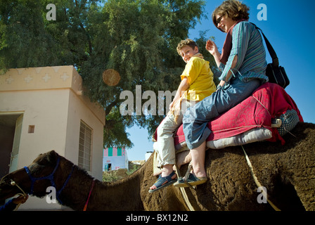 Mother and son sitting on a camel in the Thar Desert, near Bikaner, Rajasthan, India - Stock Photo