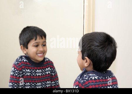 Cute toddler looking into mirror, laughing - Stock Photo