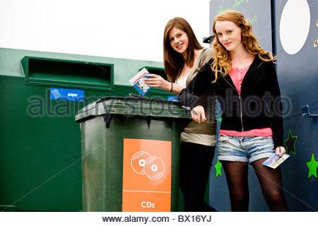 Two teenage girls recycling cds - Stock Photo