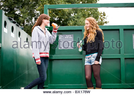 Two teenage girls standing next to a recycling container, drinking soft drinks - Stock Photo