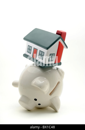 PIGGY BANK BALANCING HOUSE ON BACK RE HOUSEHOLD BUDGETS SAVINGS HOME OWNERSHIP CASH WAGES HOME BUYERS MORTGAGES - Stock Photo
