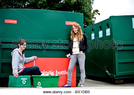 Two teenage girls standing next to a recycling container - Stock Photo