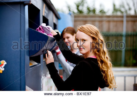 Two teenage girls recycling clothes - Stock Photo