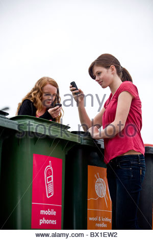 Two teenage girls using their mobile phones in a recycling center - Stock Photo