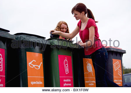 Two teenage girls recycling a mobile phone - Stock Photo