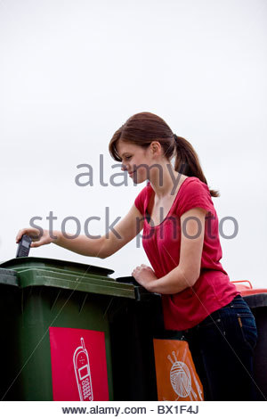 A teenage girl recycling a mobile phone - Stock Photo