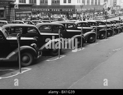 Vintage photo taken in 1938 of a row of cars parked diagonally in front of a series of parking meters in Omaha, - Stock Photo