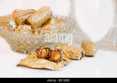 Gold foil wrapped pieces of Almond Roca candy are placed in a crystal bowl with an unwrapped candy in front. - Stock Photo