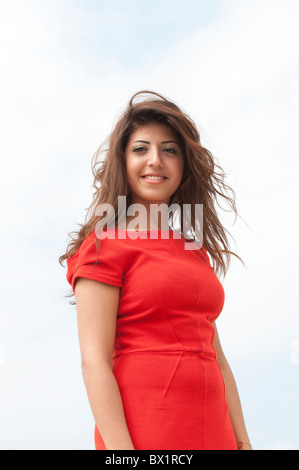 Beautiful young woman in red dress standing outdoors smiling - Stock Photo