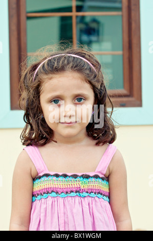 Beautiful little girl standing outside her house in pink dress Stock Photo