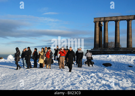 A party of  tourists taking photographs at the National Monument on Calton Hill in Edinburgh after an early December - Stock Photo