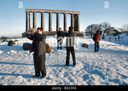 Tourists taking photographs at the National Monument on Calton Hill in Edinburgh after an early December snowfall. - Stock Photo